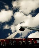 Firemen Spraying Water From Ladder Above Building — Stock Photo
