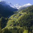 Stock Photo: Distant View Of Alpine Village In Valley Surrounded By Snow Capped Mountains