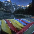 Stock Photo: Row Of Upturned Canoes And Mountain Scenery, Moraine Lake, Banff National Park, Alberta, Canada