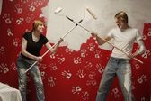 Couple Dueling With Paint Rollers — Stock Photo