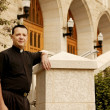 Stock Photo: Priest Standing Outside Church