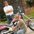Stock Photo: Father Watches Son Polish Motorcycle