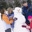 Family Builds A Snowman — Stock Photo #31695977