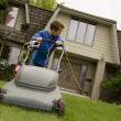 Stock Photo: Boy Pushing Lawnmower