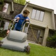 图库照片: Boy Pushing Lawnmower