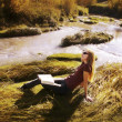 Stock Photo: WomReading On River Bank