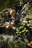 Boy Sitting By Pond — Stockfoto