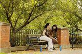 Dwóch młodych kobiet siedzi na ławce w parku — Zdjęcie stockowe