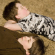 Stock Photo: Boys Laying On Ground