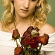 Stock Photo: Young Woman With Withered Roses