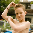 Stock Photo: Boy Feeling His Bicep