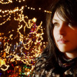 Young Woman Beside Christmas Lights — Stock Photo