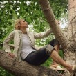 Stock Photo: WomSitting On Tree Branch