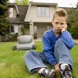 Stock Photo: Boy Sulks And Avoids Mowing Lawn