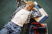 Boy Laying On Floor Listening To Music While Doing Homework — ストック写真