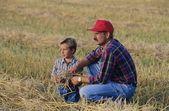 Farmer And Son In Field — Stockfoto