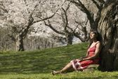Woman Relaxing Under Cherry Tree Blossoms — Stock Photo