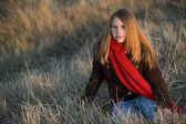 Teenage Girl Wearing A Red Scarf Sitting In A Grass Field — Foto Stock