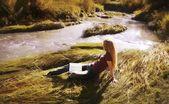 Woman Reading On Riverbank — Stock Photo