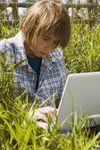Tonåring med laptop i högt gräs — Stockfoto