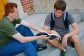 Two Young Men Sitting On Steps Discussing The Bible — Stock Photo