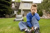 A Boy Sulks And Avoids Mowing The Lawn — Stok fotoğraf
