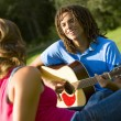 Stock fotografie: Boy Playing Guitar For Girl