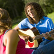图库照片: Boy Playing Guitar For Girl