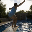 Stock Photo: Girl On Diving Board Over Swimming Pool