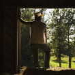 Man Wearing Work Gloves And Cowboy Hat Stands In Barn Leaning In Doorway And Looking Out — Stock Photo