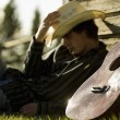 Young Man Wearing Cowboy Hat Sleeping Against Exterior Of Building With Guitar — Stock Photo