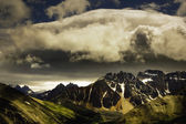 Patches Of Light Find Their Way Through Hovering Clouds Above Mountain Range — Stock Photo