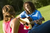 Boy Playing The Guitar For A Girl — Stock Photo