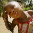 Young Girl Sticking Out Her Tongue While On The Swing Set At The Park — Stock Photo #31755757