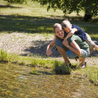 Mother Giving Son Piggyback Near Lake — Stock Photo