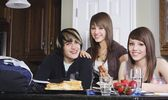 Three Friends Sitting At Dining Table, Smiling — Stock Photo