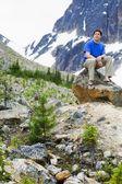 Vue de face d'un homme assis sur un rocher — Photo
