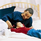 Father And Little Girl Talking On A Bed — Stock Photo