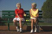 两个老年妇女坐在一起的网球拍 — 图库照片