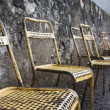 Stock Photo: Old Metal Chairs Along Stone Wall