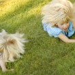 Stock Photo: Girls Rolling Down Hill