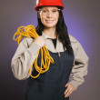 Tradeswoman In Coveralls, Holding An Extension Cord — Stock Photo #31769585