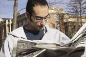 Young Man Reading Newspaper Outside — Stock Photo
