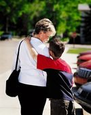Mother And Son In Parking Lot With Son's Arm Around Mother's Shoulder — Stock Photo