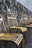 Old Metal Chairs Along A Stone Wall — Stock Photo