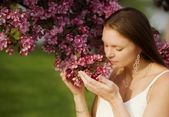 A Young Woman Smelling Flowers — Stock Photo