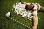 A Man Lying On Golf Balls — Stock Photo