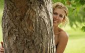 Woman Peering From Behind A Tree — Stock Photo