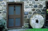 Architectural Exterior Of Stone Wall, Door And Millstone — Stock Photo