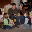 Family Reading A Story At Christmas Time — Stock Photo